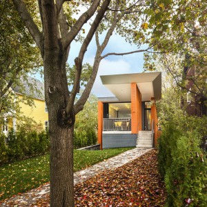 Widok na dom od frontu. Modernistyczna bryła i odważna barwa drewna przykuwa wzrok okolicznych mieszkańców. Projekt: Paul duBellet Kariouk, Kariouk Associates. Fot. Kariouk Associates.
