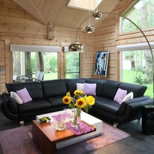 Minimalizm i prostota w zastosowanych rozwiązaniach i elementach wyposażenia sprawiają, że wszechobecne drewno nie przytłacza wnętrza. Pięknie łączy się z kanapą, oszczędnym w formie stolikiem i dekoracyjnym oświetleniem. A do tego salon, dzięki ogromnym przeszkleniom, otwiera się na otaczający dom krajobraz. Las dosłownie wnika do środka. Projekt Tomasz Motylewski, Marek Bernatowicz. Fot. Bartosz Jarosz.