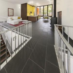Widok z mostu łączącego przestrzeń życiową z główną sypialnią (za plecami). Z lewej strony znajduje się boczne wejście u szczytu schodów, a po prawej – piecyk z tradycyjnym paleniskiem ogrzewający wnętrze. Projekt: Paul duBellet Kariouk, Kariouk Associates. Fot. Kariouk Associates.