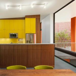 Duże, panoramiczne okna wpuszczają światło słoneczne do otwartej kuchni, dzięki czemu wnętrze jest jasne i bardziej przytulne. Projekt: Paul duBellet Kariouk, Kariouk Associates. Fot. Kariouk Associates.