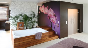 Połączona z łazienką sypialnia to prywatna strefa pana i pani domu. Naturalny, lekki styl i relaksujący klimat tworzą materiały: drewno i naturalne kamienie – otoczaki. Z kolei fantastyczna fototapeta z motywem storczyka sprawia, że wnętrze jes