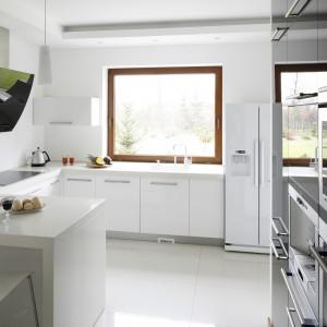 Białe meble w kształcie litery L przełamuje wysoka zabudowa z kolorze czarnym. Wszystkie fronty wykończone są lakierem w połysku, dzięki czemu kuchnia wydaje się optycznie większa. Projekt: Piotr Stanisz. Fot. Bartosz Jarosz.