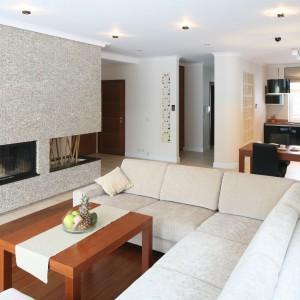 Duża, otwarta przestrzeń salonu została ściśle podporządkowana funkcji wypoczynkowej. Relaksacji sprzyjają tu zarówno ciepłe, stonowane barwy – beże i brązy, jak i naturalne, szlachetne materiały – drewno i kamień. Projekt: Karolina Łuczyńska. Fot. Bartosz Jarosz.