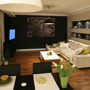 Duża, obszerna sofa to właściwy jedyny element wyposażenia tego stworzonego do wypoczynku salonu. Jej jasnobeżowy kolor doskonale prezentuje się na tle ciemnych ścian. Projekt: Lucyna Kołodziejska. Fot. Bartosz Jarosz.