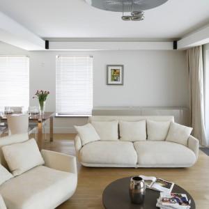 Utrzymane w minimalistycznej stylistyce wnętrze nie jest ani odrobinę chłodne. To zasługa tapicerowanych w ciepłym odcieniu beżu mebli wypoczynkowych. Ich obszerne siedziska same w sobie tworzą przytulny klimat. Projekt: Kamila Paszkiewicz. Fot. Bartosz Jarosz.