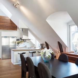Funkcjonalna kuchnia i obszerna jadalnia ze stołem dla 8 osób połączone zostały w jedną przestrzeń. Umowny podział pomiędzy pomieszczeniami stanowi kuchenna wyspa, pełniąca jednocześnie funkcję domowego baru. Fot. Per Jansson