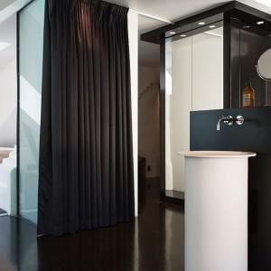 Dużą designerską łazienkę połączono drzwiami z sypialnią małżeńską. Intymność zapewnia czarna zasłona zamontowana w przejściu. Fot. Per Jansson