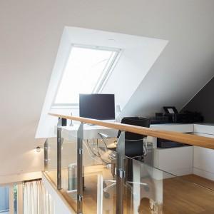 Na jednym z półpięter urządzono gabinet. Niewielką przestrzeń okalają szklane balustrady, które optycznie powiększają wnętrze, czyniąc je lekkim. Fot. Per Jansson