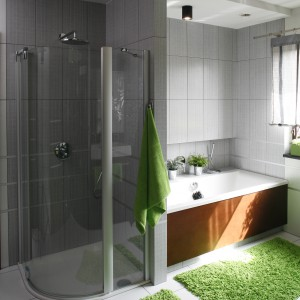 W łazience dla rodziny znajdują się zarówno prysznic i wanna, dlatego wnętrze to spełnia potrzeby wszystkich domowników. Wannę i kabinę prysznicową ulokowano obok siebie - rozdziela je ścianka, która następnie przechodzi w podwieszany sufit. Projekt: Anna Gruner. Fot. Bartosz Jarosz