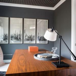 W gabinecie panuje wysmakowana elegancja w nowoczesnym stylu: meble o prostej formie, brak zbędnych zdobień. Na ścianie grafika oprawiona w cztery symetryczne ramy. Ze współczesną stylistyką kontrastuje wzorzyste wykończenie sufitu i okalające go sztukaterie. Fot. Refined.