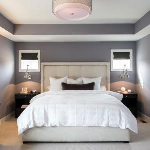Wysokie łóżko z tekstylnym zagłówkiem wkomponowano pomiędzy dwie nocne szafki. Nad meblami zaplanowano oświetlenie sztuczne i naturalne. To ostatnie ma postać niewielkich okienek z urokliwymi roletami, dopasowanymi kolorystycznie do mebli. Fot. Refined.