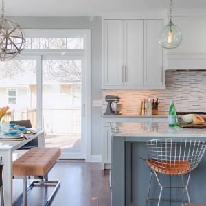 Duże przeszklenia w kuchni doświetlają otwarte wnętrze oraz wydzielają przestrzeń pomieszczenia, zaplanowaną jako jadalnia. Fot. Refined.