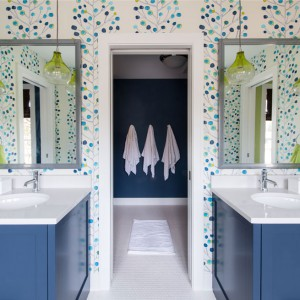 Żywe, energetyzujące kolory, motywy roślinne na ścianach, niebieskie meble i żółte klosze na wiszących lampach. Tak wygląda przestrzeń drugiej łazienki. Estetyczną równowagę zapewniają biała podłoga i blaty. Fot. Refined.