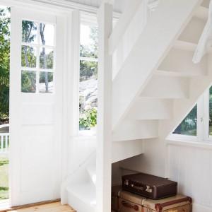Niewielką przestrzeń pod schodami zagospodarowano jako schowek do przechowywania np. starych kufrów. Te z kolei same w sobie również są ozdobą wnętrza. Fot. Stadshem.