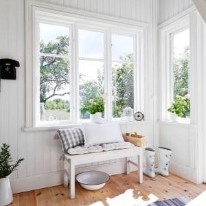 Po przekroczeniu progu domu jesteśmy witani przez urokliwy hol. Kontrastujący ze ścianami czarny vintage'owy telefon, rośliny na parapetach okien i ława obłożona poduszkami uczyniły z tego przechodniego pomieszczenia piękną przestrzeń. Fot. Stadshem