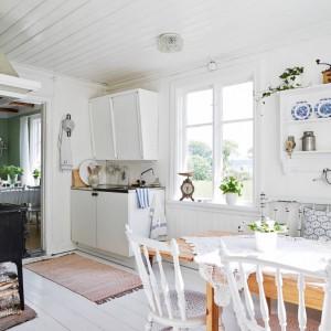 W kuchni dominującym kolorem jest biały, ocieplony brązowymi akcentami w postaci drewnianego, niemalowanego stołu i małego chodniczka na podłodze. Zlokalizowaną pod ścianą ławę wyłożono poduszkami, kolorystycznie komponującymi się z porcelaną, którą udekorowano wiszące półki. Fot. Stadshem.