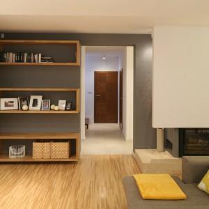 W urządzonym w minimalistycznym stylu salonie główne miejsce zajmują nowoczesny kominek, wygodna kanapa i przestronne półki na książki. Czegóż chcieć więcej do miłej lektury? Projekt: Luiza Jodłowska. Fot. Bartosz Jarosz.