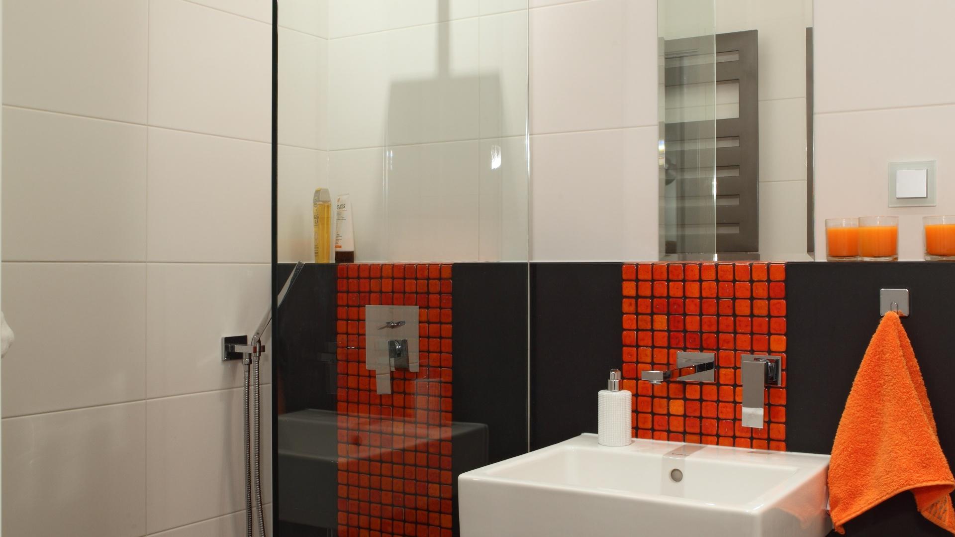 Sposobem na funkcjonalne wykorzystanie przestrzeni jest otwarta wnęka prysznicowa z odpływem w posadzce. Prysznic od reszty pomieszczenia oddziela tafla szkła, przez co łazienka wygląda przestronnie. Powierzchnia:  3,5 m kw. projekt: Michał Mikołajczak. Fot. Monika Filipiuk-Obałek.