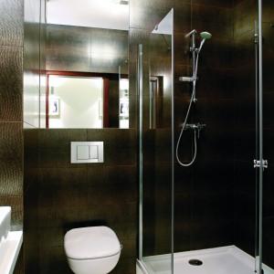 Z powodu niewielkich wymiarów łazienki wyposażenie zostało ograniczenie do minimum, a z dekoracji zrezygnowano w ogóle na rzecz efektownych płytek z faktura a la skóra węża. Mimo to zmieściły się - oprócz sanitariatów, kabiny prysznicowa, szafki podumywalkowej także pralka i kosz na bieliznę (na prawo od wejścia). Powierzchnia: ok. 3,5 m kw. Projekt: Małgorzata Brewczyńska. Fot. Bartosz Jarosz.