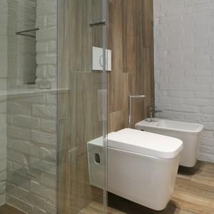 Wąska ścianka boczna oraz otwierane wahadłowo drzwi tworzą kabinę prysznicową. Zamiast  brodzika – odpływ liniowy wposadzce. Fot. Bartosz Jarosz