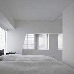W sypialni małżeńskiej dominuje biel. Geometryczna forma ścian i gładkie fronty szafy nadają wnętrzu futurystycznego charakteru. Fot. Koichi Torimura.
