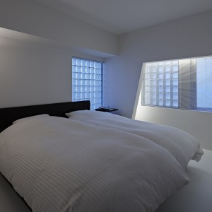 Sypialnia właściwie pozbawiona jakichkolwiek dekoracji. Rolę elementu dekoracyjnego przejmuje wysoka stojąca lampa oraz szklane luksfery w otworach ściennych. Całość ujmuje eleganckim szykiem i minimalizmem. Fot. Koichi Torimura.