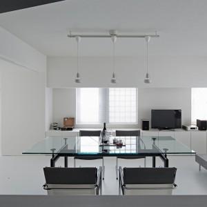 Stół ze szklanym blatem, metalowa duża lampa i betonowa ława wpisują się idealnie w nowoczesną stylistykę wnętrza. Fot. Koichi Torimura.