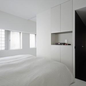 Choć na pierwszy rzut oka, w sypialni nie ma nic więcej poza łóżkiem i małą półką, do dyspozycji domowników jest szafa, zgrabnie schowana za gładkimi frontami, pozbawionymi uchwytów. Fot. Koichi Torimura.