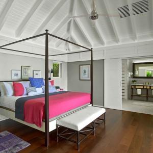 Różowa narzuta i dekoracyjne poduszki łagodzą biało-szarą sypialnię. Fot. Luis Pons Design Lab.