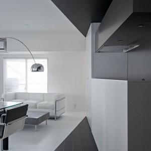 Kuchnię od jadalni oddziela wysoki blat kuchenny, na którym zlokalizowano zlewozmywak i kuchenką. Pozostają one całkowicie niewidoczne, schowane za monolityczną białą powierzchnią. Innym elementem umownie oddzielającym pomieszczenia jest podłoga - w salonie i jadalni biała - przy kuchni wyłożona czarną okładziną. Fot. Koichi Torimura.