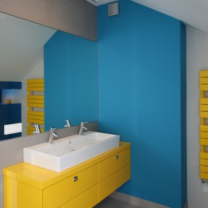 Na tle  niebieskich ścian wyeksponowano szafkę w słonecznym, żółtym kolorze. Podwieszana szafka jest na tyle duża, że mieści podwójną umywalkę. Projekt: Małgorzata Galewska. Fot. Bartosz Jarosz.