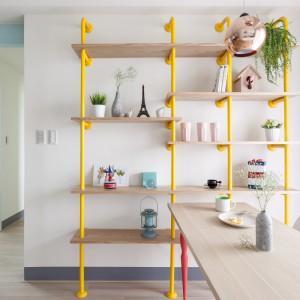 Półki w kuchni wykonano z różowych rurek wpuszczonych w ścianę i podłogę oraz zamontowanych na nich drewnianych desek. Stylistycznie pasują do całego mieszkania, przy czym wizualnie tworzą lekkie wrażenie, nie przytłaczając przestrzeni. Projekt: HAO Design Studio. Fot. Hey! Cheese.