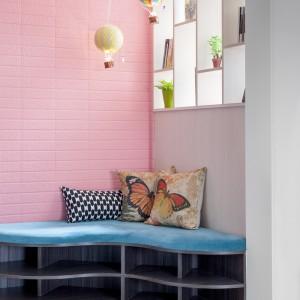 W rogu pomieszczenia zrealizowano kącik wypoczynkowy. Zabudowę meblową pokryto miękkim materiałem w niebieskim kolorze. Nad podłogą kilka praktycznych półek do zagospodarowania. Przestrzeń doświetla światło wpadające przez półki na przestrzał zlokalizowane na ścianie. Projekt: HAO Design Studio. Fot. Hey! Cheese.