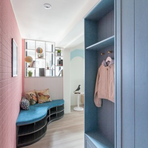 Strefę wejściową tworzy szafa, pomalowana na kolor baby blue oraz przytulny kącik wypoczynkowy. Projekt: HAO Design Studio. Fot. Hey! Cheese.