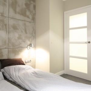 Chłodne wnętrze ociepla tapicerowane łóżko w tkaninie. Stanowi również fajny kontrast dla betonowej ściany. Projekt: Lucyna Kołodziejska. Fot. Bartosz Jarosz.
