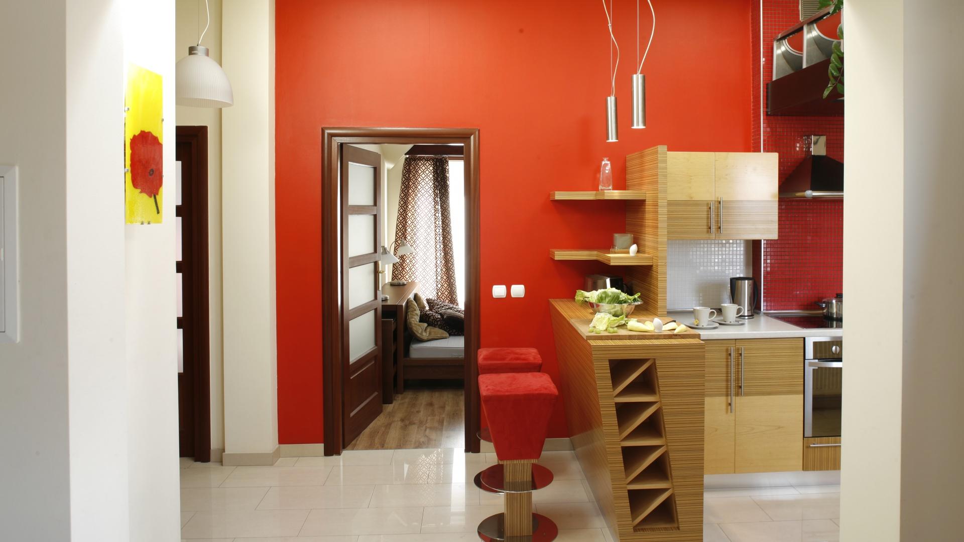 Czerwona ściana to odważny krok, który jednak w tym wnętrzu się opłacił. Przestrzeń nabrała oryginalnego charakteru. Projekt: InsideLab. Fot. Bartosz Jarosz.