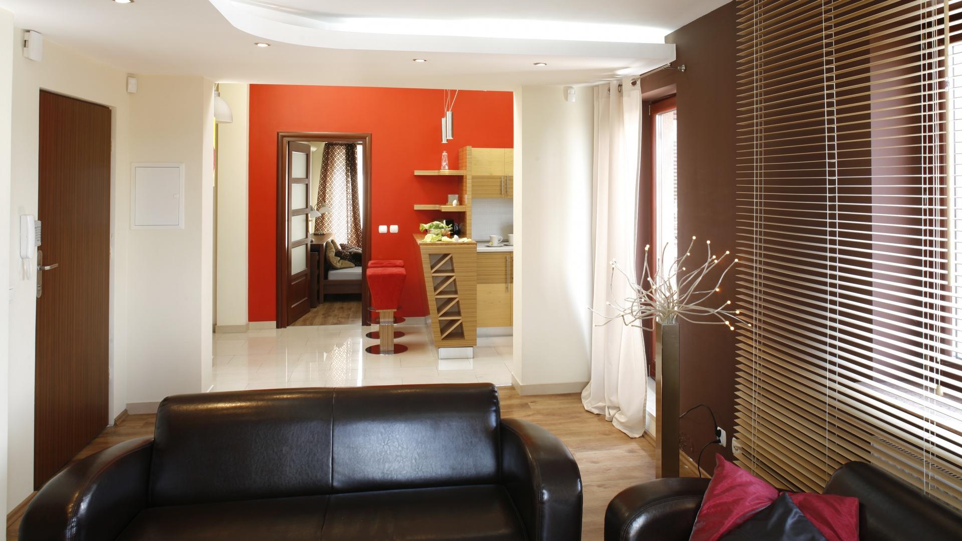 Czarne, eleganckie sofy w salonie doskonale prezentują się w otoczeniu czerwieni. Projekt: InsideLab. Fot. Bartosz Jarosz.