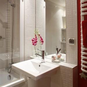 Czerwona ściana za grzejnikiem nawiązuje do kolorystyki kuchni i podobnie, jak drewno ociepla wnętrze. Projekt: InsideLab. Fot. Bartosz Jarosz.