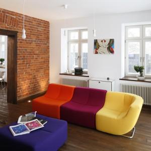 """Salon to przestrzeń, w której doszło do zderzenia elementów autentycznej architektury """"retro"""" z wyposażeniem, inspirowanym wzornictwem lat 60. i 70. XX wieku. Wysokie okna, stylizowane grzejniki, podłogę z surowych desek i odsłoniętą, ceglaną ścianę, zestawiono z awangardowymi, neonowymi meblami wypoczynkowymi. Projekt Konrad Grodziński. Fot. Bartosz Jarosz."""