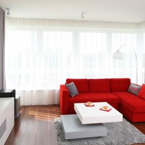 Niewielki apartament urządzono w jasnej i bardzo modnej kolorystyce. Dominują tu biele i szarości, których monotonię przerywają czerwone akcenty. W strefie wypoczynkowej jest nim wygodny narożnik. Projekt Iza Szewc. Fot. Bartosz Jarosz.