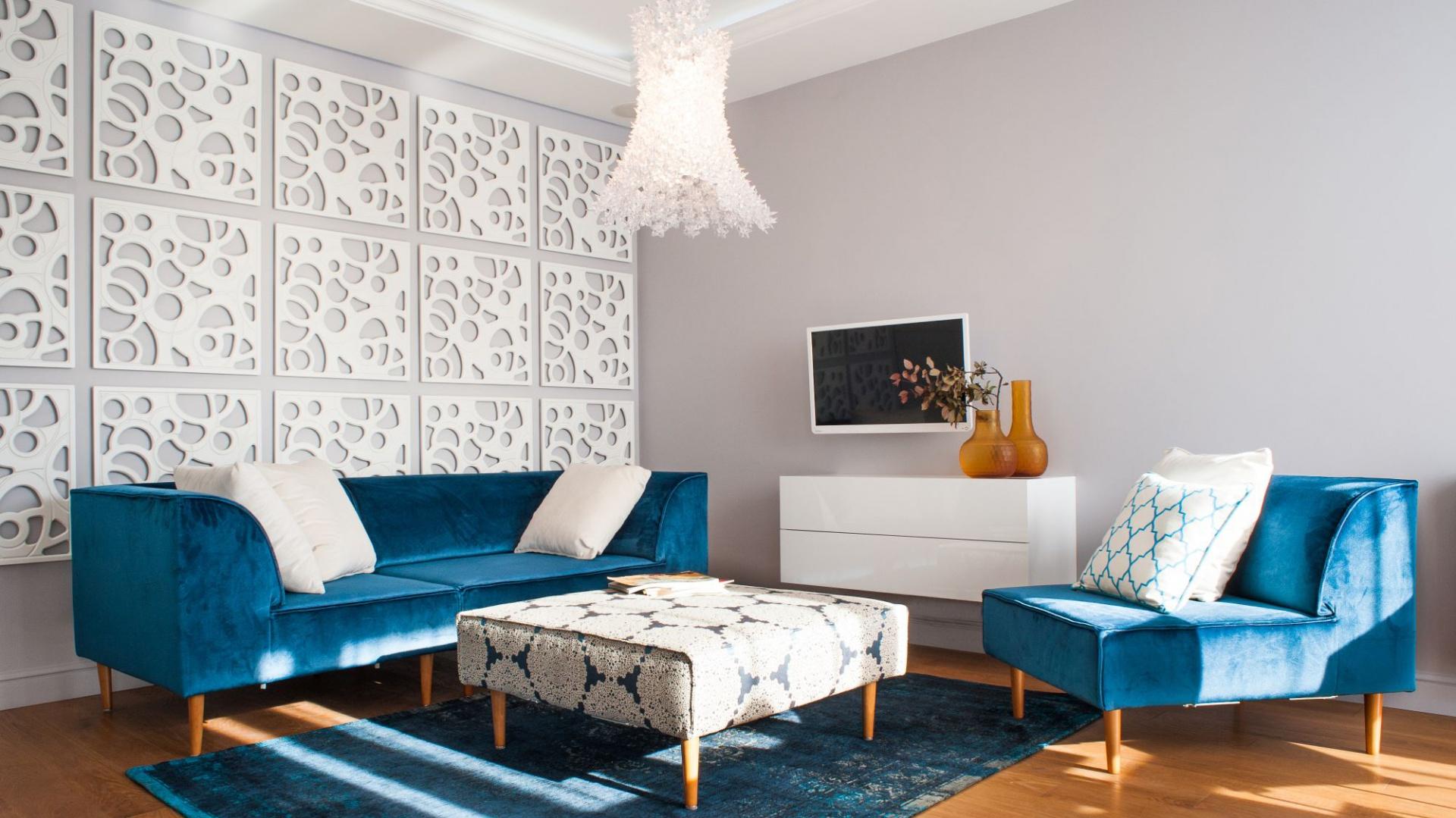 Pokój dzienny skomponowano z bieli oraz różnych odcieni niebieskiego. Turkusowe meble wypoczynkowe doskonale się prezentują na tle wyłożonej ażurowymi panelami ściany. Projekt Arkadiusz Grzędzicki. Fot. Adam Ościłowski, panadam.pl