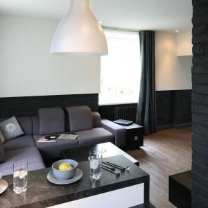 Czarno-biała kolorystyka buduje męski charakter przestrzeni. Podkreśla go bar, który wyznacza granicę między kuchnią i salonem. Najbardziej wyrazistym elementem wystroju wnętrza jest jednak pomalowana na czarno cegła. Projekt: Dominik Respondek. Fot. Bartosz Jarosz.