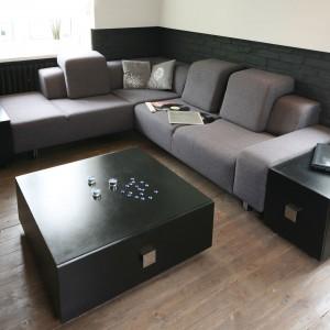 Przestrzeń salonu zdominowała duża, narożna kanapa usytuowana na tle przyzdobionej cegłą ściany. To idealne miejsce na filmowy maraton przy mocnym drinku. Projekt: Dominik Respondek. Fot. Bartosz Jarosz.