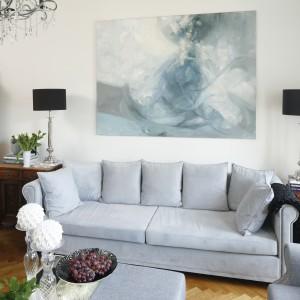 Niepowtarzalny klimat wnętrza budują liczne elementy dekoracyjne. Jednym z nich jest duży obraz utrzymany w pięknej palecie jasnoszarych barw. Projekt: Iwona Kurkowska. Fot. Bartosz Jarosz.