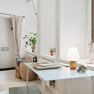 Pozbawione zasłon i firan okna pozwalają na praktyczne zagospodarowanie wnęk okiennych oraz nadają wnętrzu sterylnego, oszczędnego wyrazu. Przysłonić można natomiast drzwi wejściowe, nad którymi zawieszono romantyczną, beżową zasłonę. Fot. Alvhem Makleri.