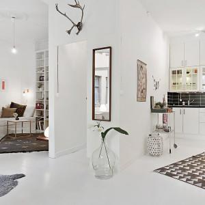 Mieszkanie stanowią jeden przestronny pokój i łazienka. W otwartej przestrzeni dominuje biel, dodatkowo optycznie powiększająca wnętrze. Fot. Alvhem Makleri.