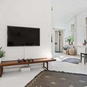 Na ścianie bezpośrednio naprzeciw narożnej kanapy powieszono telewizor. Kącik wypoczynkowy - zamiast tradycyjnej szafki RTV -  uzupełnia drewniana ława. Fot. Alvhem Makleri.