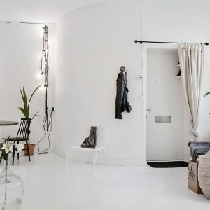 Naprzeciw okien powieszono lustro w drewnianej ramie. Kolor naturalnego drewna ociepla wnętrze, podczas gdy tafla lustra odbija widok za oknem i wpadające do mieszkania światło. Dzięki temu zabiegowi, zyskano efekt powiększonej wizualnie przestrzeni. Fot. Alvhem Makleri.