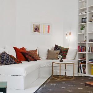 W rogu pomieszczenia zlokalizowano narożną białą kanapę, którą ożywiają kolorowe wzorzyste poduszki. Bliskie sąsiedztwo biblioteczki zachęca do relaksu z książką. Fot. Alvhem Makleri.
