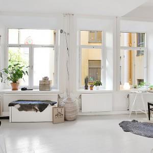 Zlokalizowane w jednym rzędzie, wysokie podwójne okna zapewniają nieograniczony dopływ naturalnego światła do wnętrza mieszkania. Fot. Alvhem Makleri